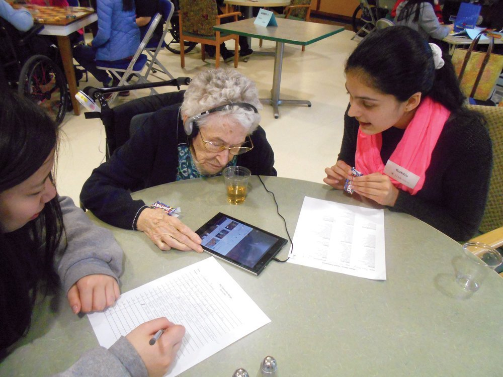 Music Links: Students help a senior friend discover her favourite music using a tablet and headsets.Photo courtesy LINKages.